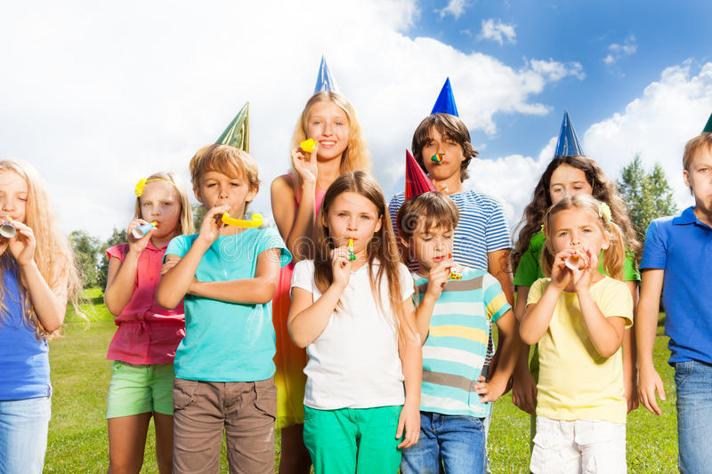 Big birthday. Large group of kids age 5 to 11 outside on a birthday party blowing noisemakers horns and twisted whistles royalty free stock photography