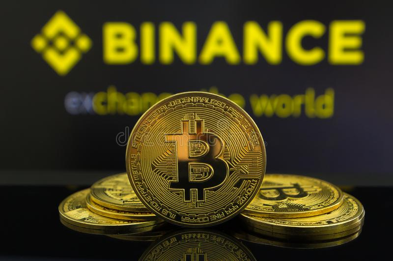 A big Bitcoin cryptocurrency coin in the centre and other bitcoin coins from both side in front of Binance crypto market . The royalty free stock images