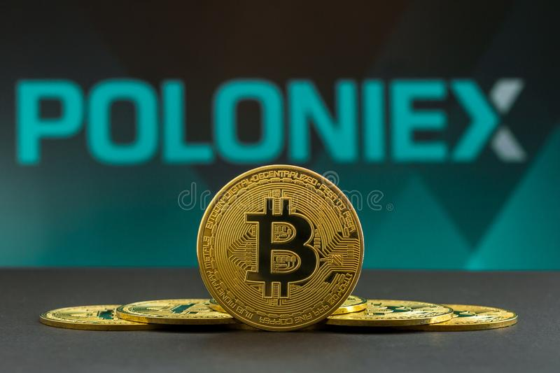 A big Bitcoin cryptocurrency coin in the centre and other bitcoin coins from both side in front of Poloniex crypto market . The stock photo