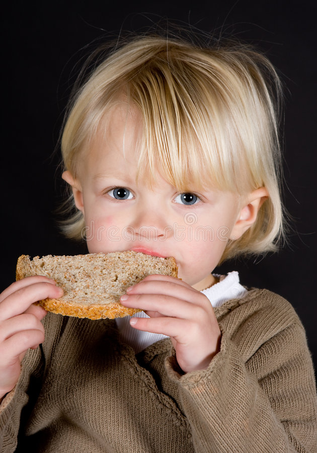 Big bite. Little cute blonde girl taking a big bite at lunch stock images