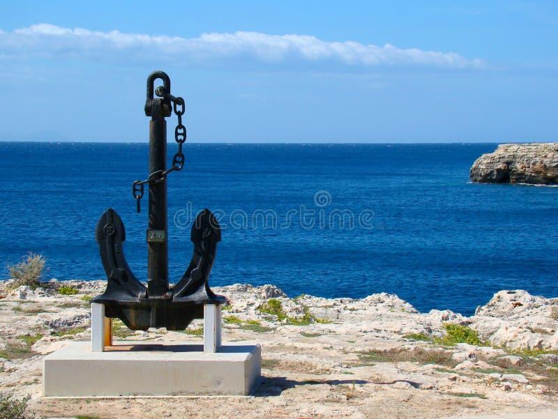 A big black anchor located on the coast. Ciutadella, Menorca royalty free stock photos