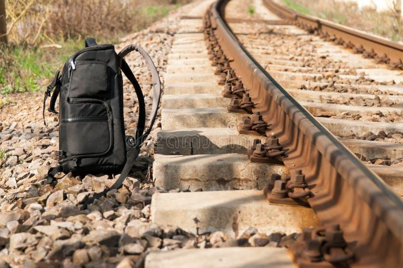 Big black back pack near rail road tracks royalty free stock images