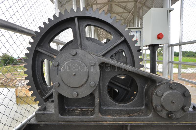 Big black cog for control the floodgate. New big black cog machine for shutdown or opening controling the floodgate of reservoir royalty free stock photos