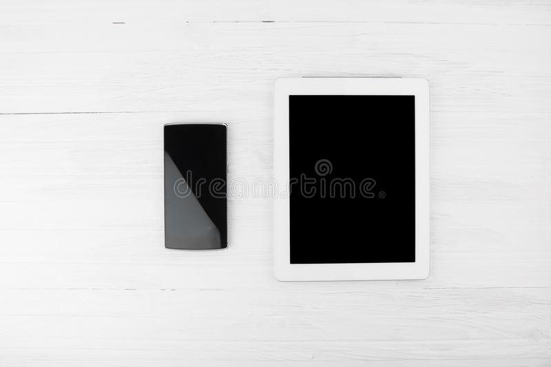 Big Black Empty Screen Smart Tablet Device Next To Smart Phone O stock photo