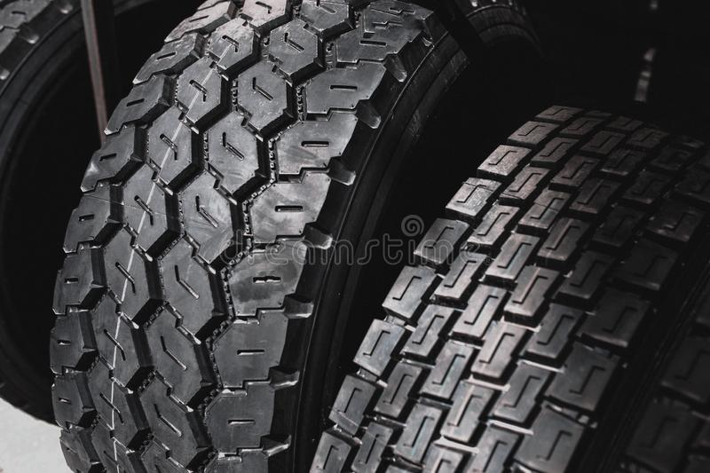 Big black huge big truck, tractor or bulldozer loader tires wheel close-up on stand, shop selling tyres for farming and big vehicl royalty free stock image