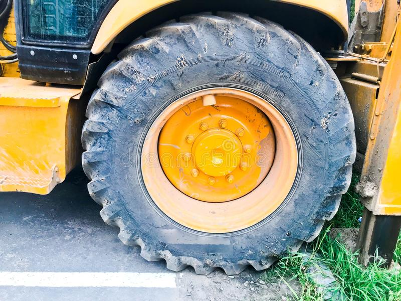 Big black wheel with tire and tire with tread for a large powerful iron construction orange excavator. Construction machinery, stock image