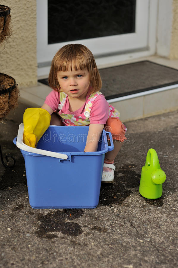 Big Blue Bucket. A young girl playing with a blue bucket royalty free stock image