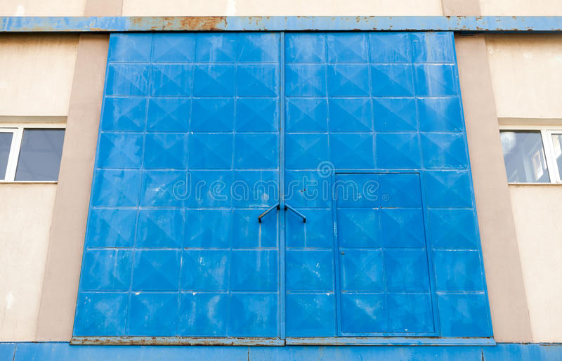Big blue closed metal gate of Industrial building stock photo