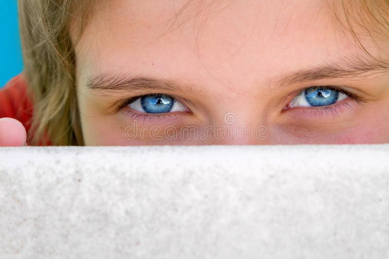 The Big Blue Eyes of a Young Girl Peer at the Camera Over the Ed stock photo
