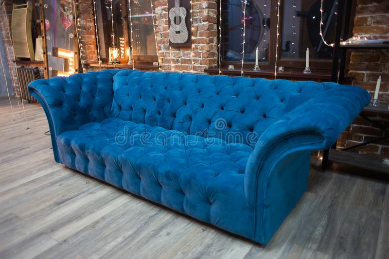 Big blue sofa in an interior. Upholstered furniture for the house royalty free stock photos