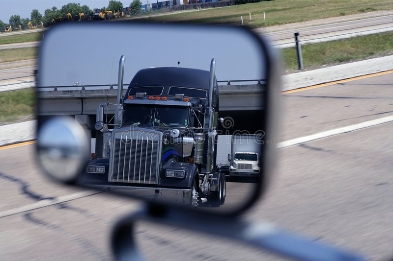 A big blue truck in the vehicle mirror. Transportation stock photography