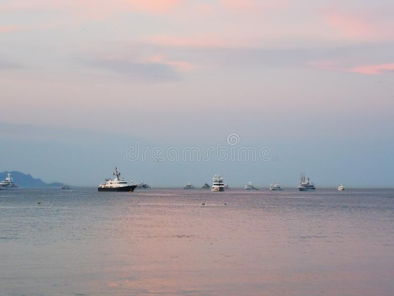 Big boats in the ocean anchored during a beautiful pink sunset on holidays in St tropez france stock photo