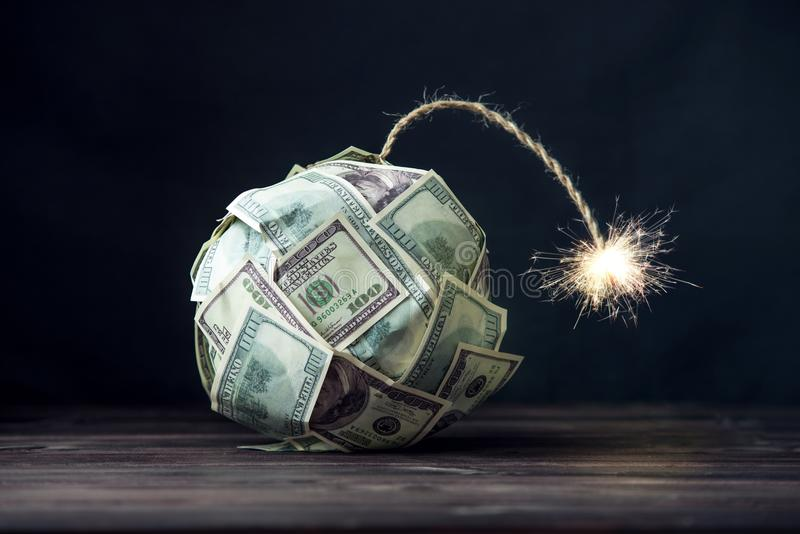Bomb of money hundred dollar bills with a burning wick. Little time before the explosion. Concept of financial crisis stock image