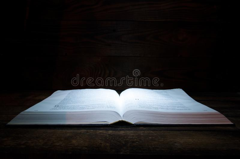 The big book of the Bible lies on a wooden table. In the dark. A light shines on the book from above. stock photos