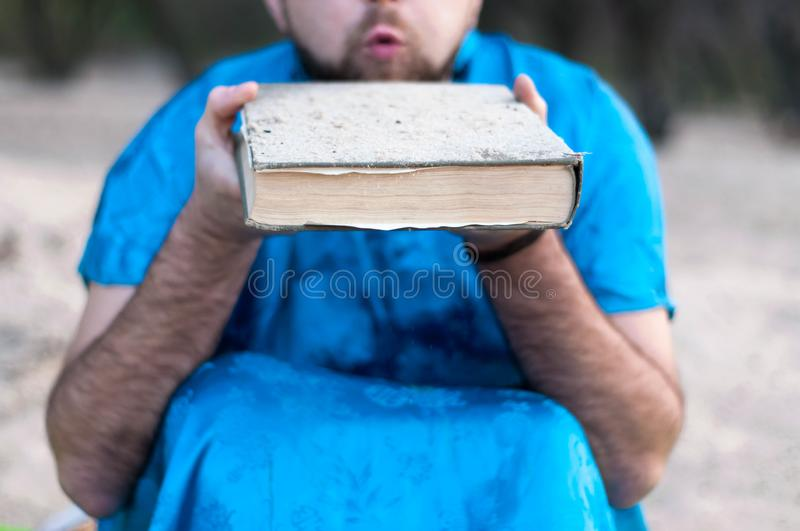 Big book in man hands blowing sand from book on beach royalty free stock photography