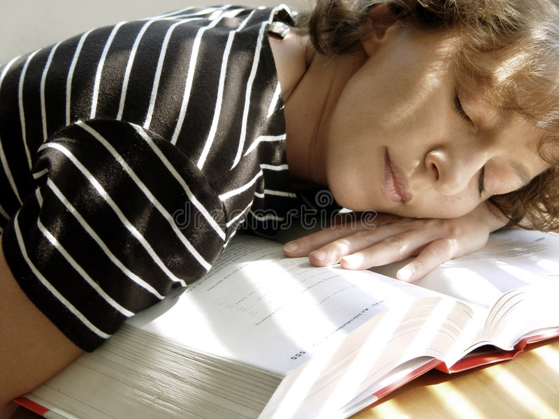 Big Books. Tired girl is sleeping on her book royalty free stock photography