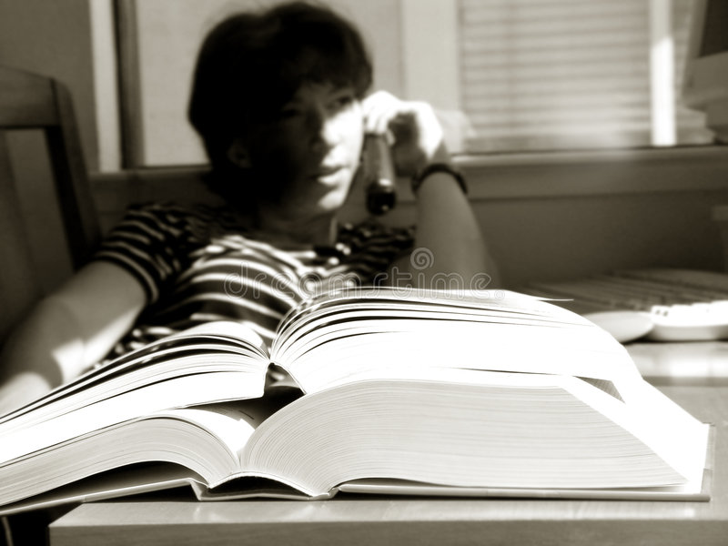 Big Books. Girl is doing her homework and talking on the phone royalty free stock images