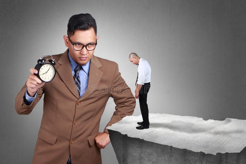 Time Discipline Concept. Big Boss with serious face caught latecomer. Businessman holds clock in hand angry to employee for being late. Time discipline concept royalty free stock photo