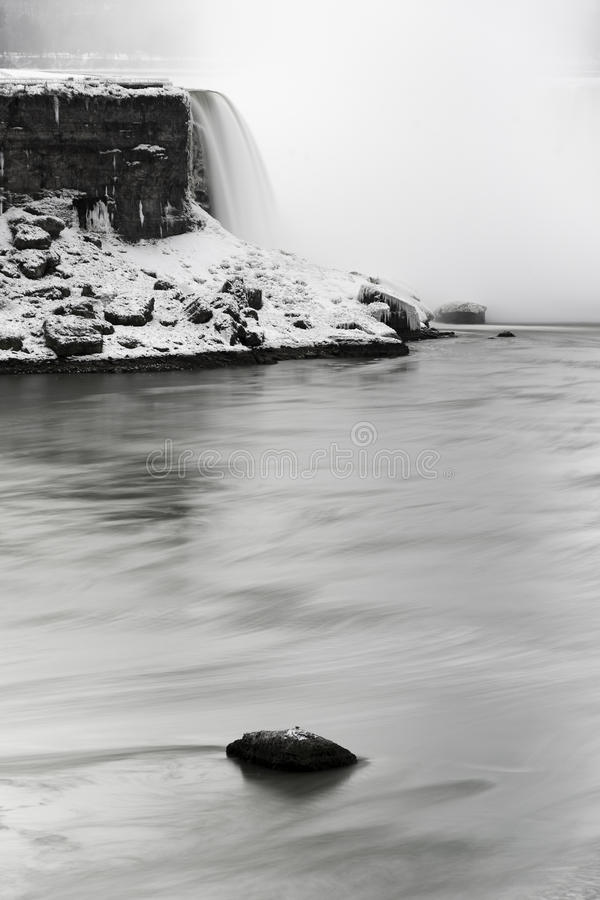 Big boulder rock in the middle of a swift river, large waterfall. In the background, black and white stock photography