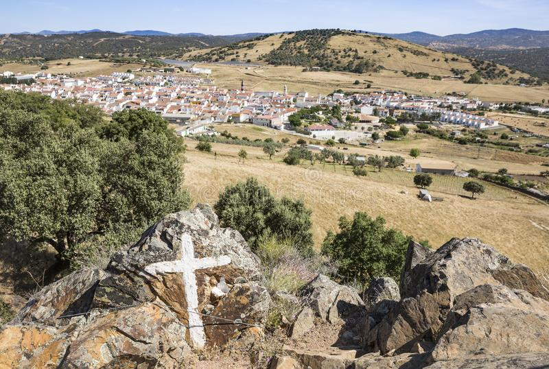 Big Boulders with a painted cross and a view over Almaden de la Plata town stock photography