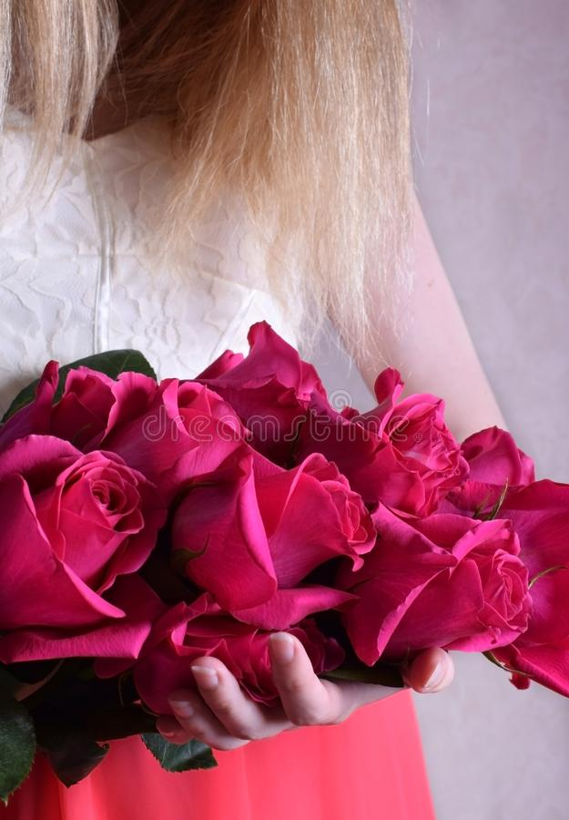 Big bouquet of pink roses held by a young woman. Wearing a dress royalty free stock photo