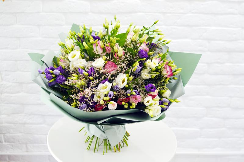 Big bouquet of wild wild flowers in salon of flowers. On a white background. Flower beautiful background. Wild wild flowers in stylish paper. Gentle flowers in royalty free stock photos