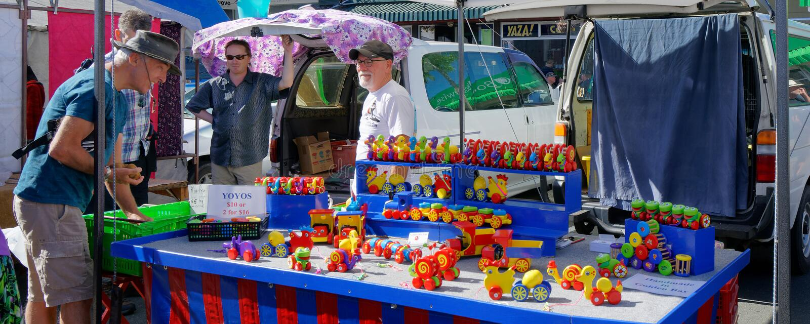 Big boy enthralled by the painted wooden toys on a Nelson market stall royalty free stock photo