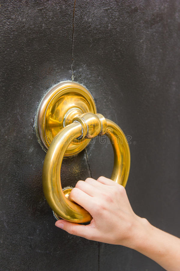 Big brass knock-ring. Fair, small female hand holding a golden door knocker ring on a door in Modena, Emilia-Romagna, Italy stock photo