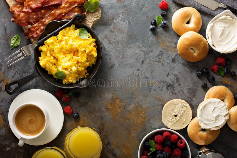 Big breakfast with bacon and scrambled eggs. Big breakfast with bacon, bagels and scrambled eggs on the table overhead with copy space stock photos