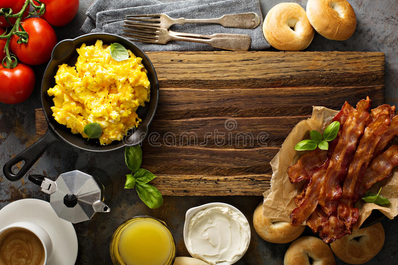 Big breakfast with bacon and scrambled eggs. Big breakfast with bacon, bagels and scrambled eggs on the table overhead with copy space royalty free stock photos