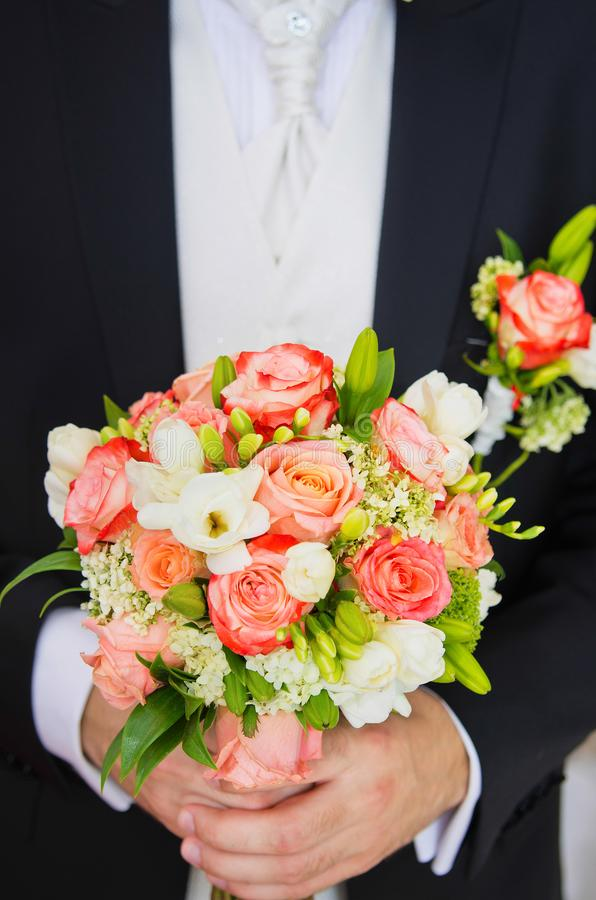 Big bridal bouquet. Of white and orange fresh flowers in hands of groom in black suit. Vertical color photography stock image