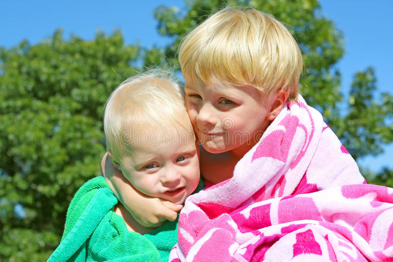 Big Brother Hugging Baby Outside. A young child is hugging his baby brother as they sit outside in the grass in beach towels on a sunny summer day stock images