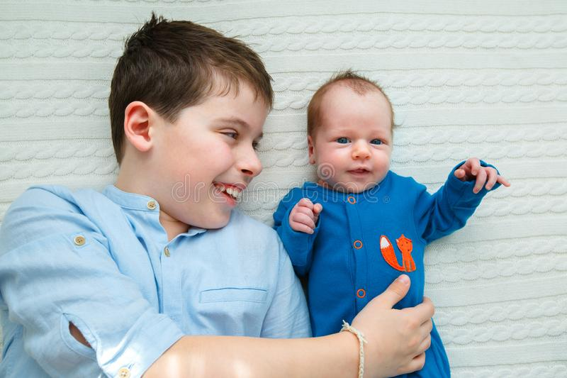 Big brother hugging his newborn baby girl. Toddler kid meeting new sibling stock photography