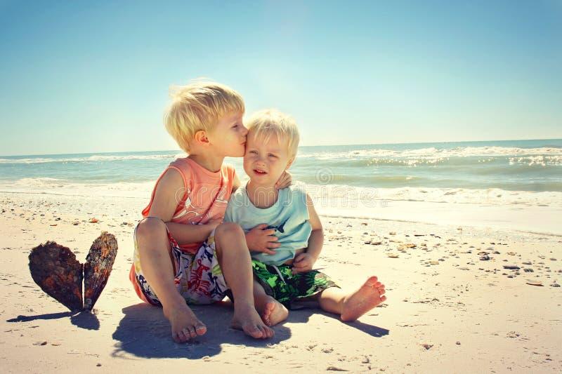 Big Brother Kissing Young Child på stranden royaltyfri fotografi