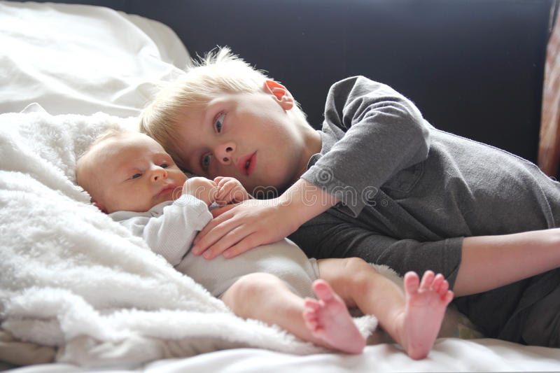 Big Brother Lovingly Playing with Newborn Baby Sister. A big brother is lovinly hugging his newborn baby sister as they lay in bed together stock photography