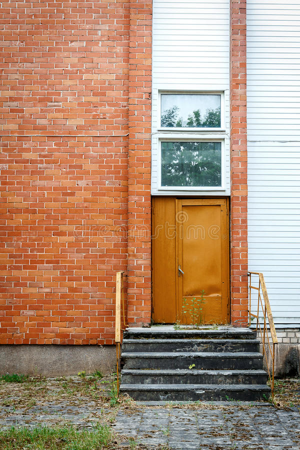 Download Big Brown Door On A Red Brick And White Planks Wall Stock Image - Image: 83708733