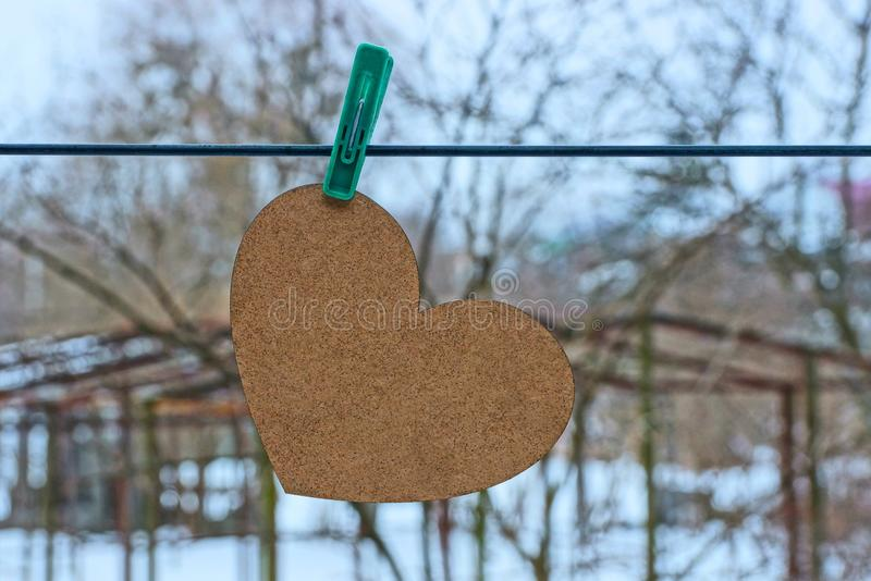 Big brown heart hanging on clothespin on street wire. Big gray heart hanging on a clothespin on a wire on the street stock photos