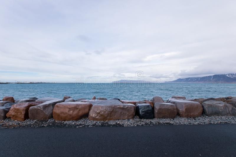 Big brown rocks and stones on the seashore on a moody cloudy day. The big brown rocks and stones on the seashore on a moody cloudy day royalty free stock photography