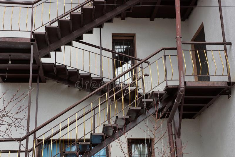 Big brown staircase on a gray building wall with windows and a door. A big long brown staircase on a gray building wall with windows and a door stock images