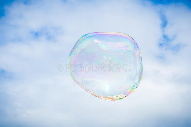 Big bubble of bubble maker flying in the air on sky background royalty free stock image