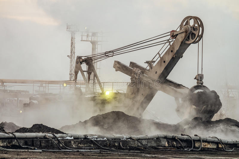 Big bucket excavator works in a outdoors dust dump. Industrial background stock photography