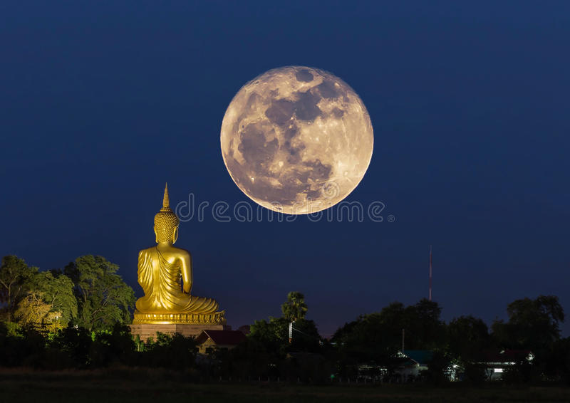 Big buddha statue in temple at night with super moon. Big buddha statue sitting in thai temple at night with super moon royalty free stock photo