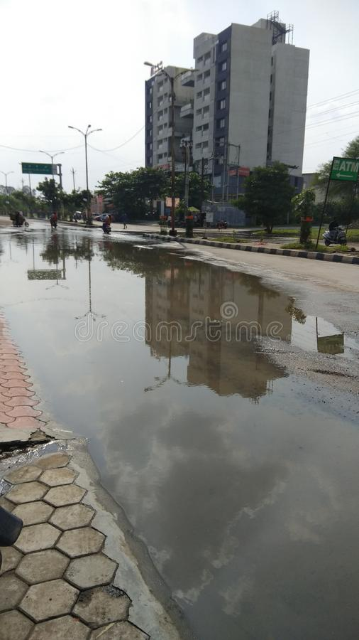 Big building reflection in waterlogged puddle during monsoon royalty free stock image