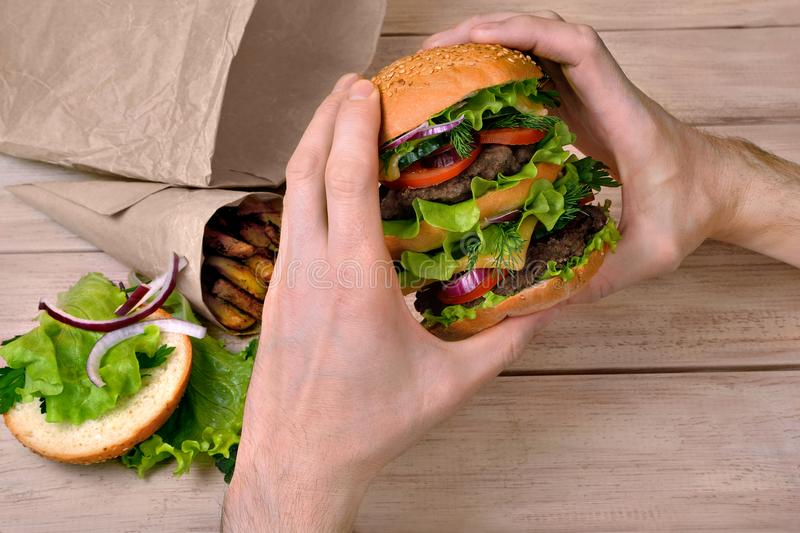 Big burger in the hands of a man at lunch time stock photography