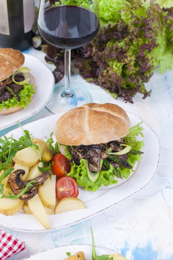 Big burger with salad and potatoes. A glass of red wine. Tasty dinner. Junk food. Text. Copy space. Big burger with salad and potatoes. A glass of red wine royalty free stock photography