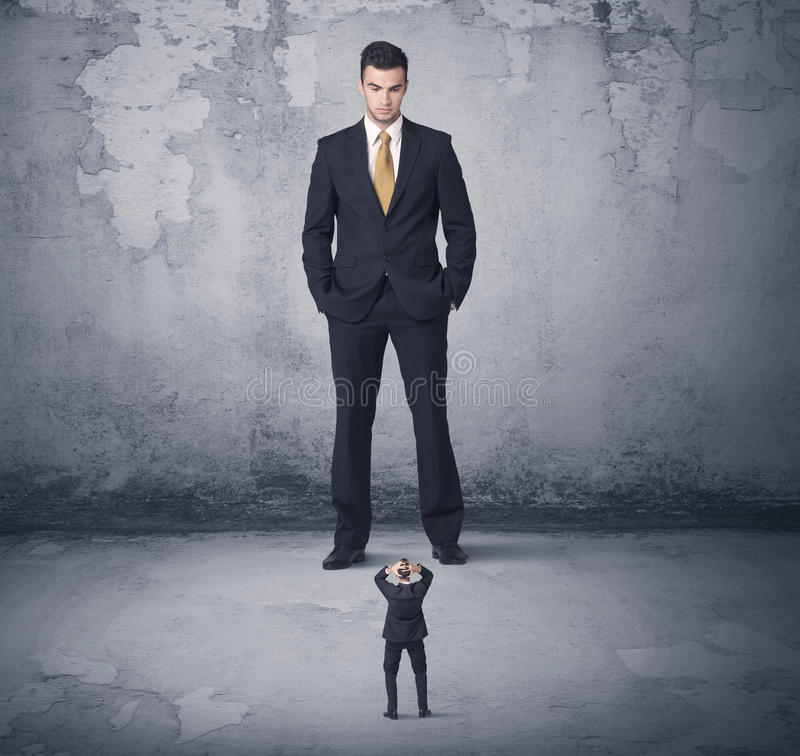 Big business bully looking at small coworker. Big angry business bully looking at small coworker concept on background royalty free stock photo