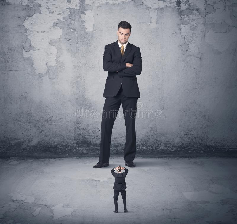 Big business bully looking at small coworker. Big angry business bully looking at small coworker concept on background royalty free stock images