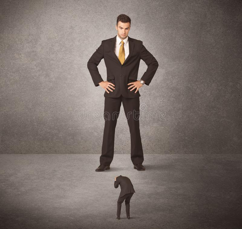 Big business man looking at small worker. Concept on background stock photo