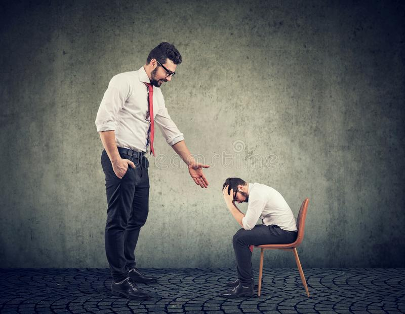 Big businessman giving a hand supporting a depressed desperate guy stock photography