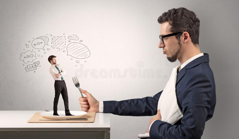 Businessman want to eat small man stock image